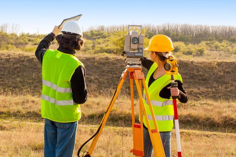 Geodeci sprawdzający teren